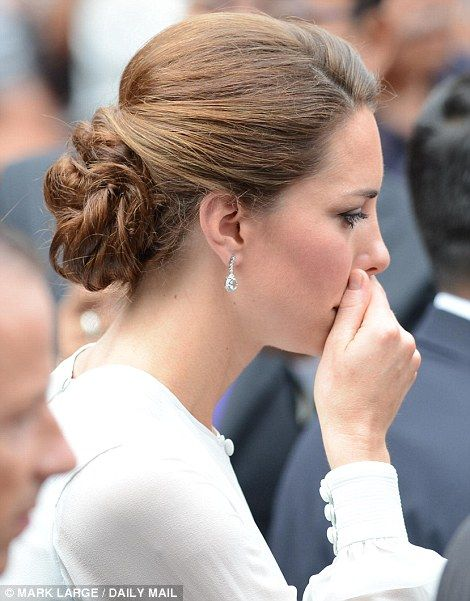 Deep in thought: Kate covers her mouth during a walkabout in Kuala Lumpar's city centre park