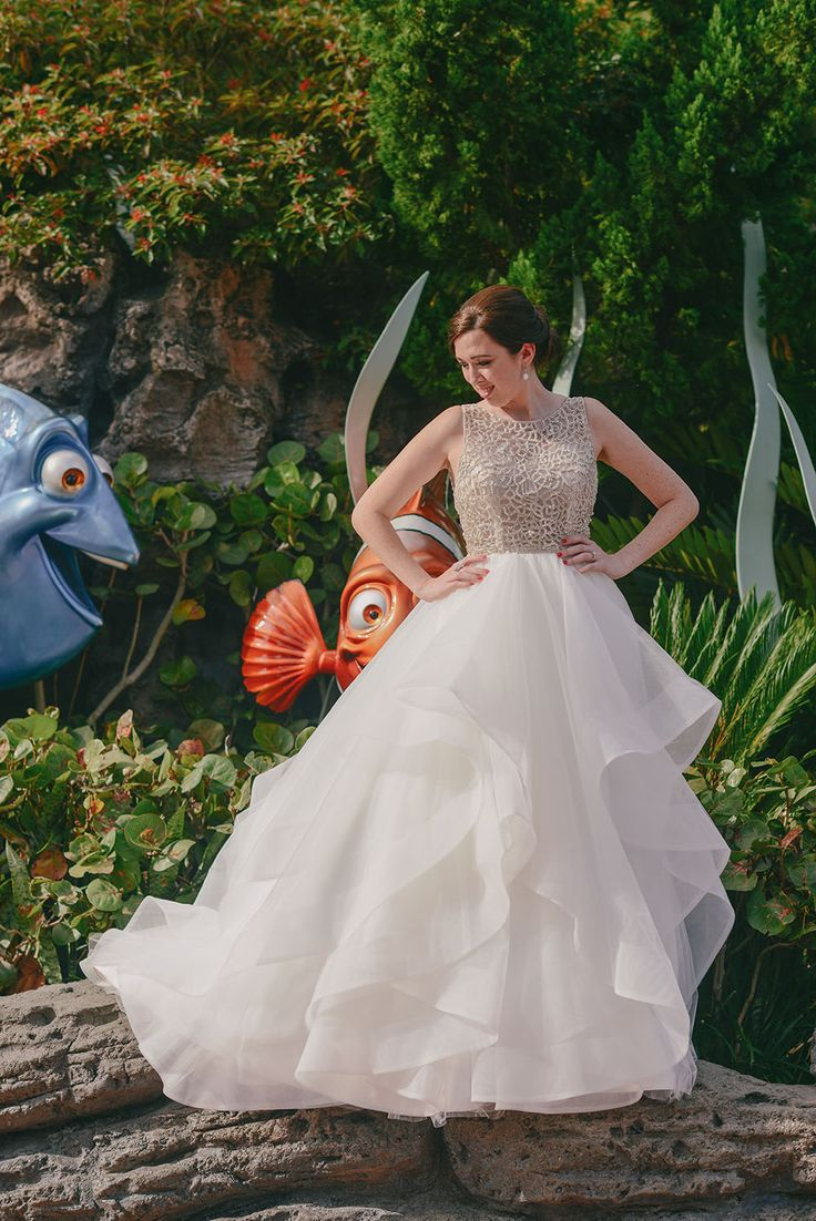 Beautiful bride outside The Seas at Epcot with some surprise guests in the background! Photo: Brittany, Disney Fine Art Photography