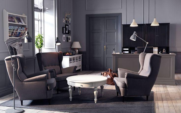 Uma receção com poltronas cinzentas e uma mesa de centro branca.