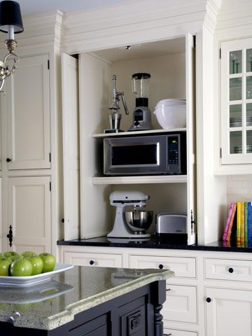 A three-level cabinet has spaces just the right height for a mixer, microwave oven, and other small appliances. Retracting doors clear the countertop when appliances are in use.