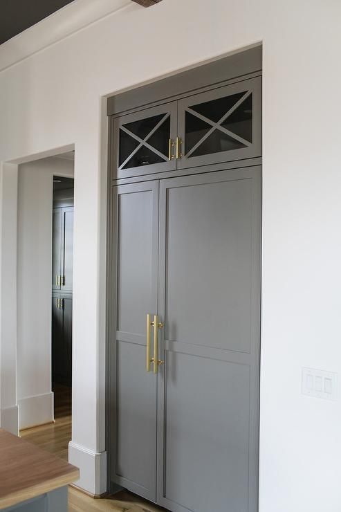 Contemporary kitchen features an inset refrigerator and freezer clad in gray paneled doors adorned in long brass handles tucked under glass x front cabinets.