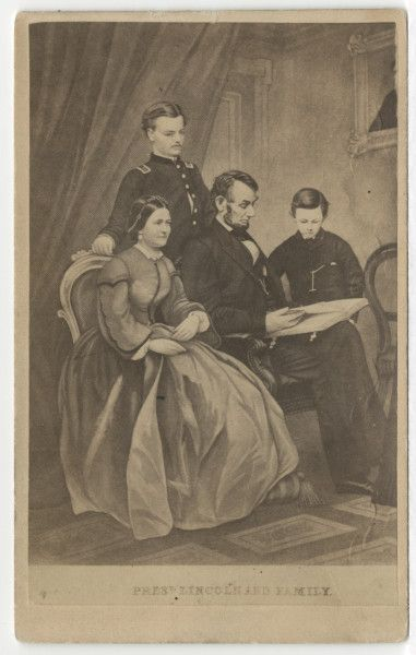 "Abraham Lincoln, seated, next to his wife, Mary, with Thomas""Tad"", 12, to the right, and Robert, 22, standing behind, in uniform. This 1865 photograph was of an engraving by Adam B. Walter based on a painting by F. Schell based on separate photographs of Robert, Lincoln and Tad, and Mary. The partially visible framed picture on the wall is Willie Lincoln, who died in 1862."