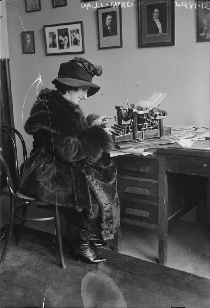 Amelita Galli-Curci seated at desk using typewritter, dressed in fur coat and hat.