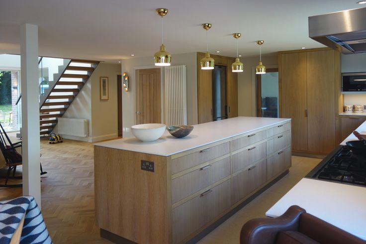 White oiled oak island unit with Silestone Blanco Norte 12mm top. Open tread staircase and herringbone parquet floor. Alvar Aalto Artek Golden Bell A330s pendants