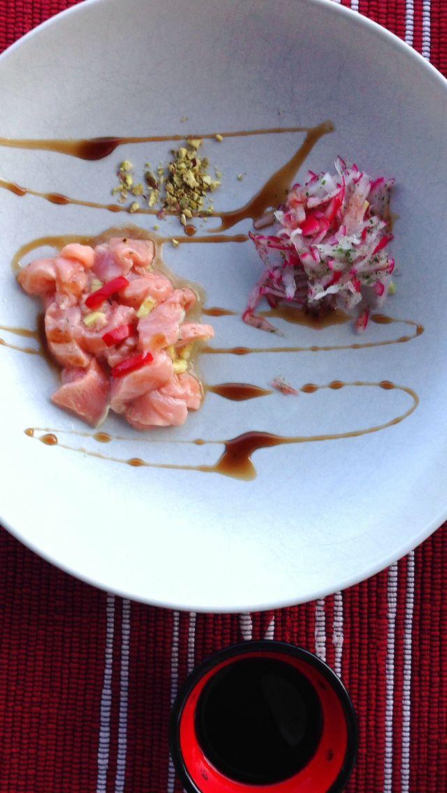 Salmon sashimi with radish, balsamico-pomegranate and pistachio.