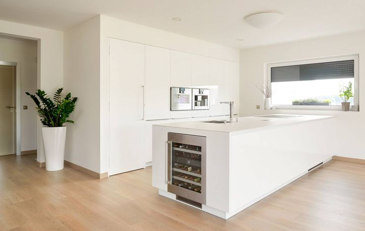 All white kitchen with a built-in wine fridge at the end of the peninsula by Hans Krug