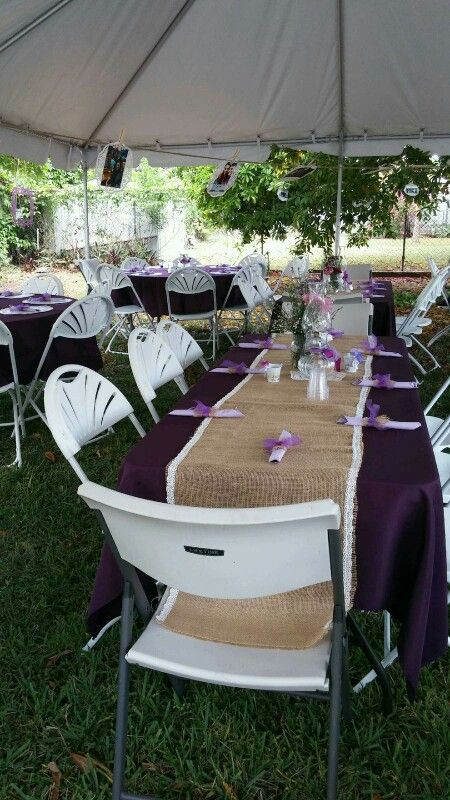 The tables has plum tablecloths and a burlap runner I made with lace edges, beautiful setting for my daughters engagement party. I had a simple centerpiece made with a lantern and I place purple ribbons Making a bow.