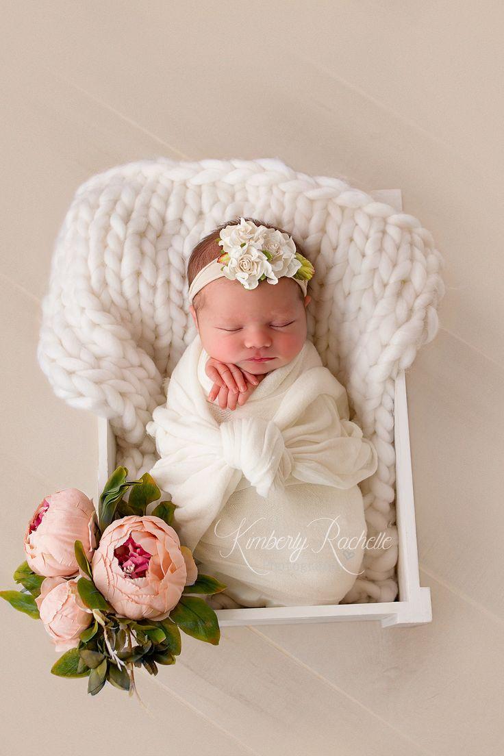 Neugeborenes Baby stellt weiße Blumen der Fotografiesitzung herrlich dar    – Babies
