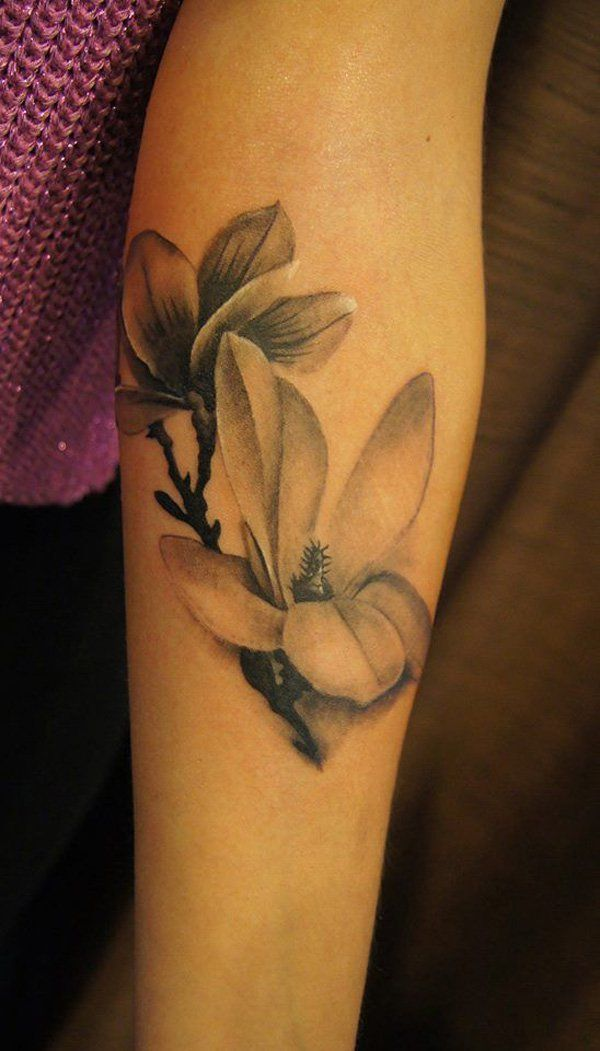 Black and white magnolia forearm sleeve tattoo in a realistic style.