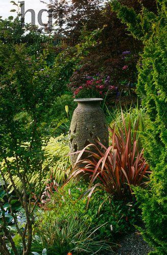 garden ornaments cork ireland. harpur garden images ltd :: empty container pot urn focal point hidden behind phormium border beside pond ornament water design: brian cross. ornaments cork ireland