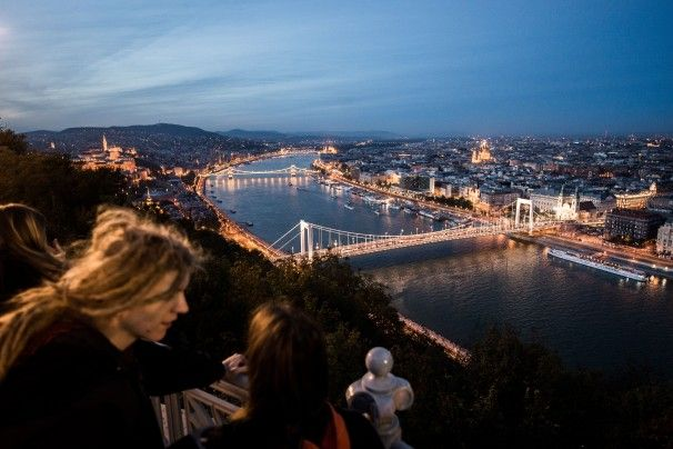 Tourists enjoy the panorama next to the Liberty Monument on Gellert Hill in Budapest.