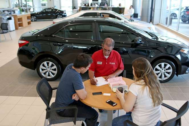 A salesman speaks with customers as they visit a Deerfield dealership on the day that Berkshire Hath... - Joe Raedle/Getty Images