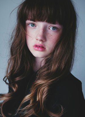 girl brown wavy hair bangs freckles blue eyes