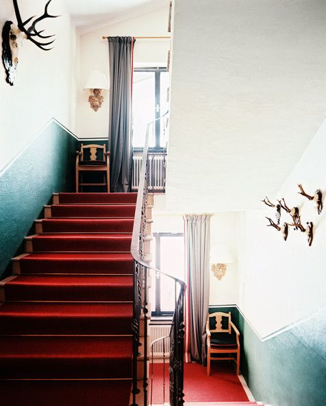 A red carpet runner and an iron banister in a stairway