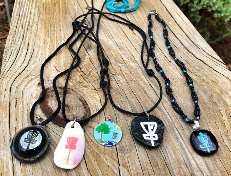 Disc golf necklaces. The artists who created these necklaces from left to right: Kristen Munoz - Asheville, NC; Erin Tivnan - Green Light Disc Golf; Kathy Hardyman - DiscDiva.com; Green Light Disc Golf; and Liz Carr.