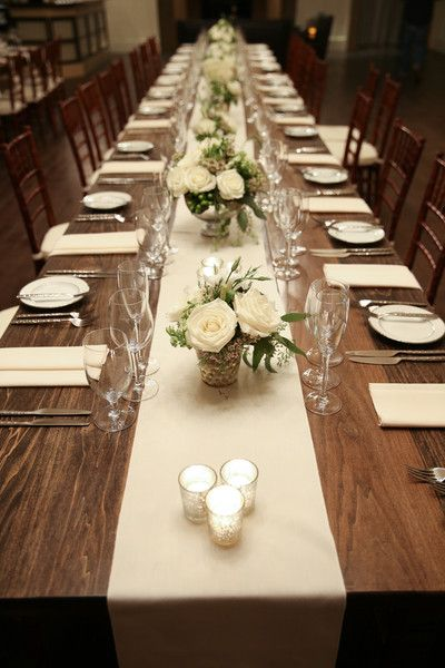 Classic ivory wedding reception decor - long wood tables with white table runners, mercury glass candles, and classic white rose centerpieces {Magdalena Stefanek Photography}