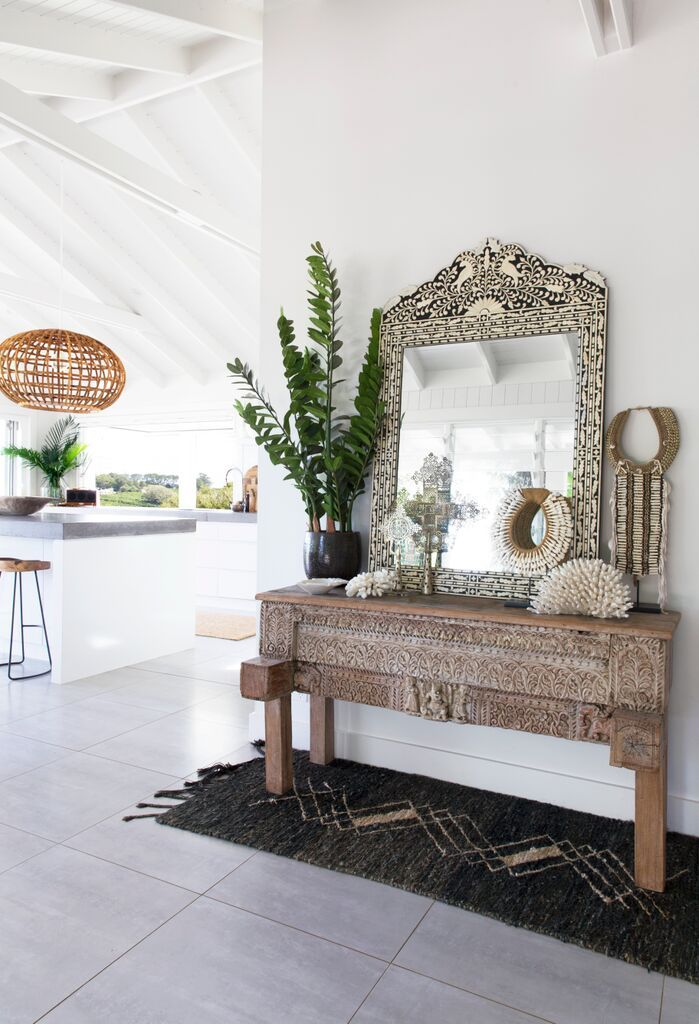 Entryway at The Grove Byron Bay. With gorgeous carved console, a bone inlay mirror and large rattan pendant lights a great mix of chosen statement pieces.