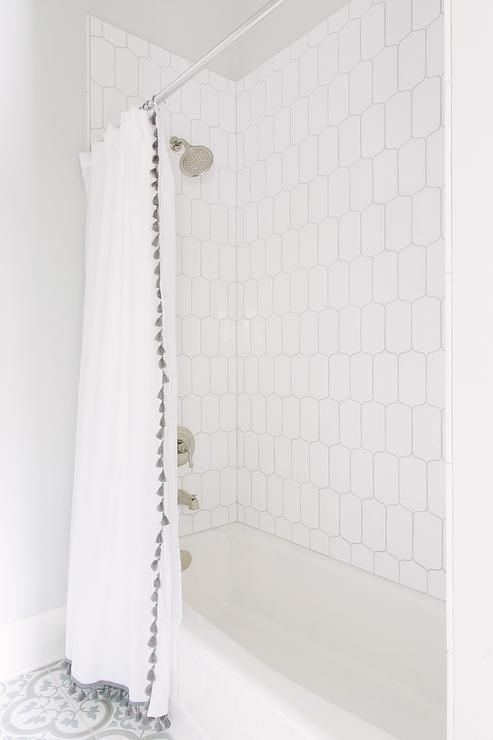 Classic white bathroom given a modern touch with patterned tiles & a unique shower curtain | Image via DecorPad | French Tassel Shower Curtain via #serenaandlily