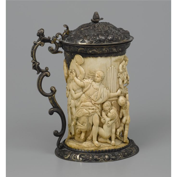 A GERMAN SILVER MOUNTED IVORY TANKARD, APPARENTLY UNMARKED, 18/19TH CENTURY the carved ivory sleeve with a relief probably depicting the Rape of the Vestal Virgins, the cover embossed with floral chasing and a bud finial, with double scroll caryatid handle height 28.5cm.