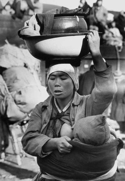 Mère coréenne allaitant son bébé, en transportant toutes ses affaires dans une bassine sur sa tête, fuyant au sud de Séoul. Guerre de Corée, 1951 Photographe : Carl Mydans #allaitement_coree