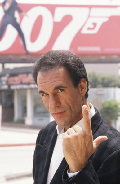 "Actor Robert Davi poses in front of a billboard on Sunset Blvd during a 1988 photo portrait session in West Hollywood, California. Davi plays a Colombian drug lord in the 1989 James Bond movie ""Licence to Kill."" (Photo by George Rose/Getty Images)"