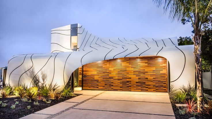 The undulating metal exterior of this family home by Los Angeles designer Mario Romano takes its cues from the movement of the ocean.
