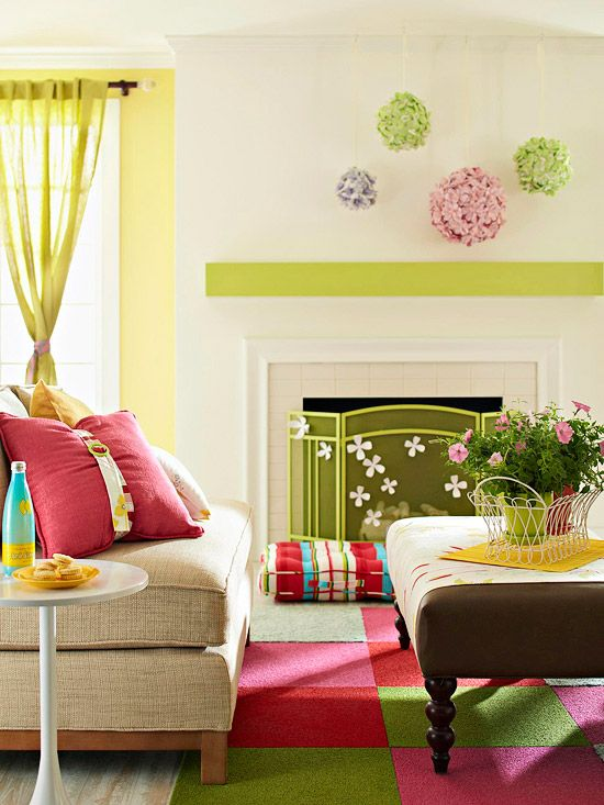Bold & Bright   Lots of bright colors and natural light in this living room make for an inviting family space. Make bold accents really pop by placing them against white backgrounds, such as the hanging flower balls above the fireplace. Opt for carpet squares that let you mix and match the colored squares to spice up a dull floor.