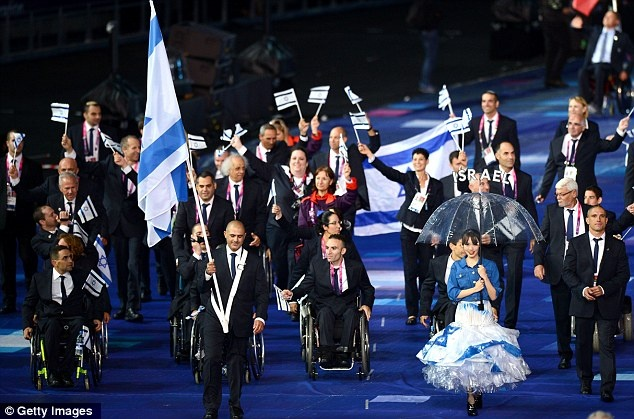 On target: Six-time paralympic shooting medallist Doron Shaziri carries the Israel flag at the head of his team