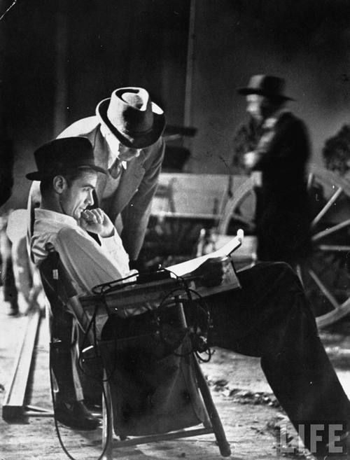 "Howard Hughes reads the script for ""The Outlaw"", 1943.  He took over directing after Howard Hawks left to direct Sergeant York.  Filming originally began in 1941."
