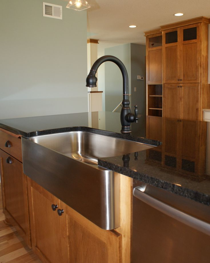 dark granite on island with stainless steel farm sink and dishwasher