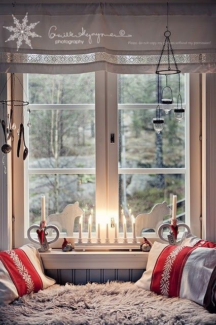 Белые фигурки и свечи украшают это окно. .