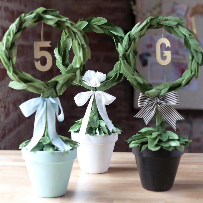 If you are planning a DIY wedding on a budget, this DIY topiary centerpiece is perfect to place on your guest tables with gold glitter paper table numbers!