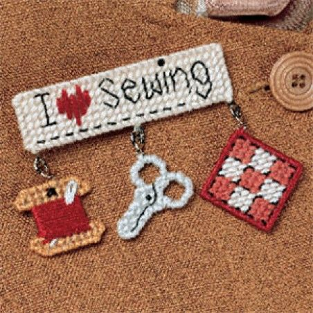 """If you want to let others know you have a notion for stitching, this lapel pin has your message all sewn up. The trio of dangling seamstress symbols will ingeniously convey your love for the hobby. The design is stitched using DMC embroidery floss and 10 mesh plastic canvas. <p><strong>Number of Designs:</strong> 1 </p><p><strong>Approximate Design </p><p><strong>Size:</strong></strong> 4""""w x 2-3/4""""h"""