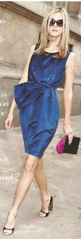 Carmen Kass con vestido entallado en la cintura; cartera fucsia, zapatos peep-toe; gafas de sol con montura de pasta, todo de Loewe. Imagen de VOGUE ESPAÑA.