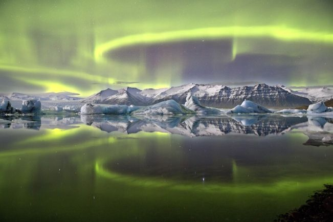 "Aurora over a Glacier Lagoon, by James Woodend, UK (2014). Overall winner and winner of ""Earth & Space"" In the background is the Vatnajökull Glacier. The pale-green glow of the aurora comes from oxygen atoms high in the atmosphere, energized by subatomic particles blasted out by the Sun. Mona Evans, ""Astronomy Photographer of the Year 2014"" http://www.bellaonline.com/articles/art184169.asp"