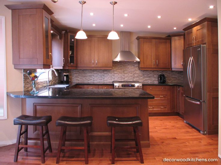 medium sized kitchen, light stain cabinets, wide framed doors, peninsula, glass backsplash and granite countertops