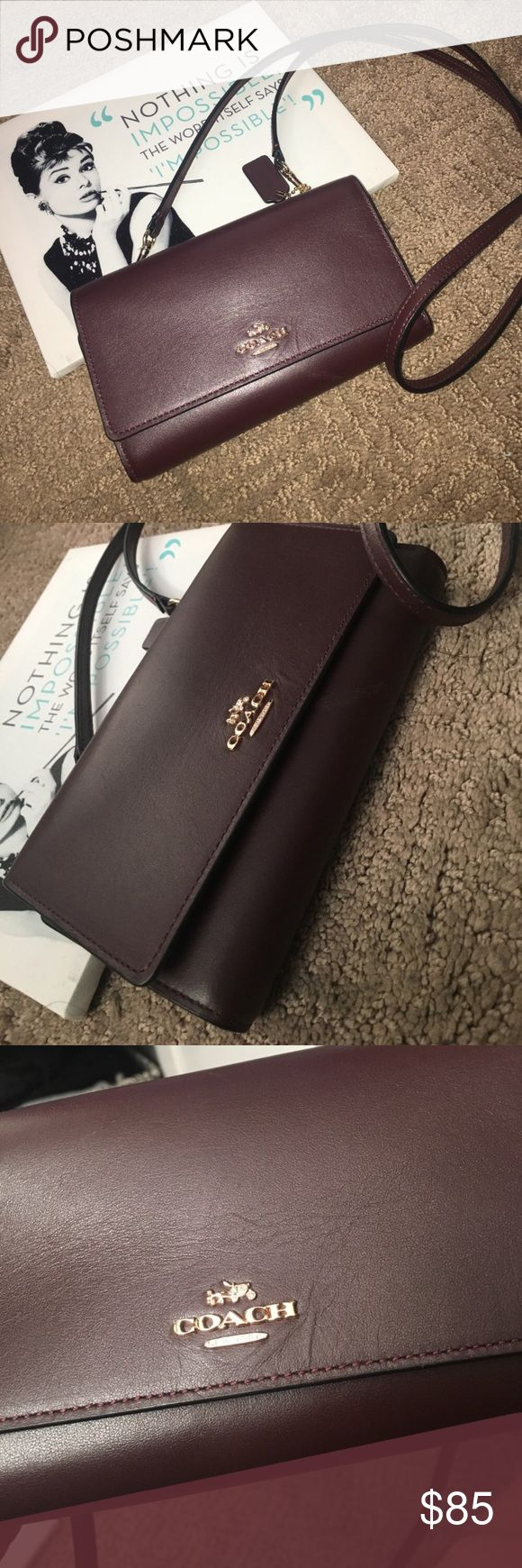 Coach phone crossbody 🌻 Excellent condition. Used only for a couple weeks. This is smooth leather. No scratches that I can see. Just alittle wrinkle in the leather nxt to the coach emblem. Color is oxblood which is a plum/wine. Gold hardware. Fits an iphone7. Strap is NOT adjustable but can be removed to use as just a wallet. Inbox with questions. These are still available from coach in other colors. This color is very rare. No low balls. No trading. 😊 Coach Bags Crossbody Bags