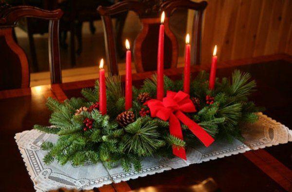des chandelles rouges et une branche de sapin naturelle au centre de la table