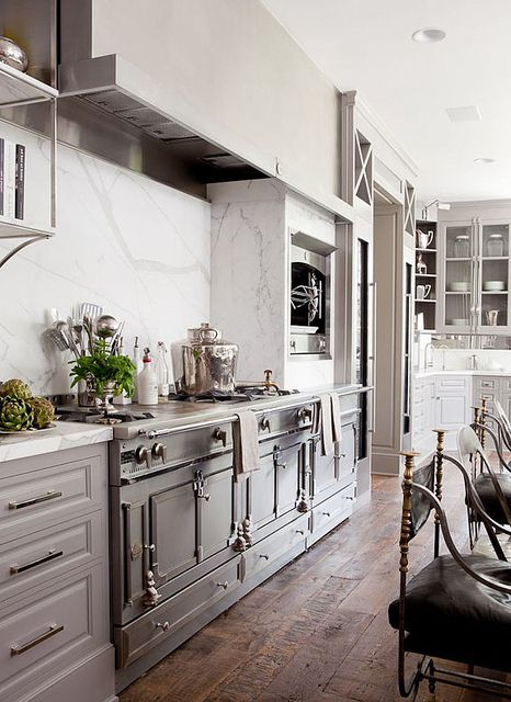 The perfect amalgam of modern and classic. The rustic oven is set into great modern style cabinets with simple lines. This works well because the oven seems ornate and needs the simplicity of the modern cabinets to keep it from getting to busy. The marble backsplash is timeless and does not take away from the focal point which is the more ornate oven. The chairs for the island are a more traditional style which balances everything out.