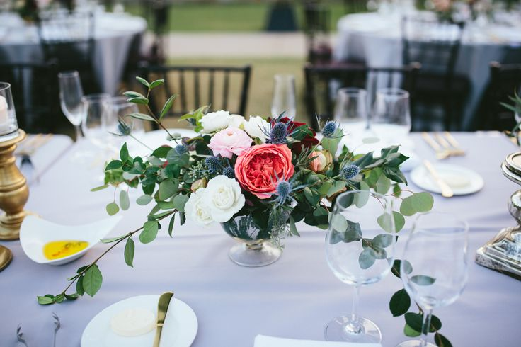 lush and loose table arrangement of pink romantic antike garden rose, white majolik spray roses, pink ranunculus, blue thistle, purple loropetalum, vines, and seeded eucalyptus in a footed mercury glass vessel on pale grey table linens.