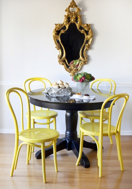eclectic dining nook or breakfast table, black painted pedestal table with pastel yellow chairs, ornate gold mirror, bright and clean with simple styling.  part of our black & gold autumn 2012 trend post on http://theunexpectedchic.com