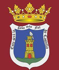 Escudo oficial de Peñafiel, sobre fondo rojo-carmesí.