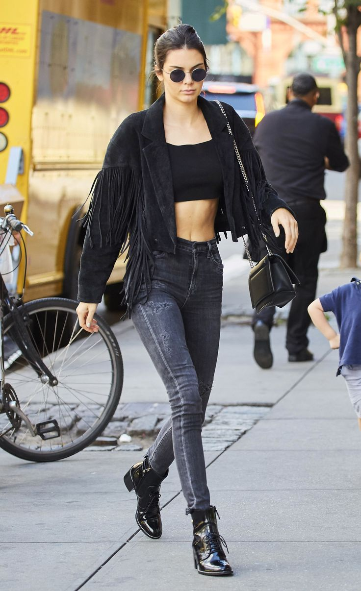 Kendall Jenner in grey high-waisted skinny jeans, black patent-leather lace up booties, a black crop top, and a black suede fringe jacket.