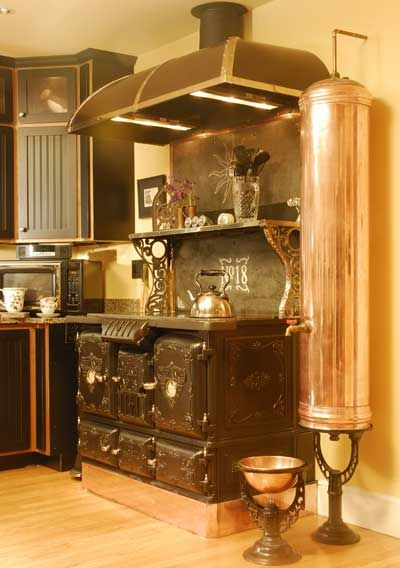 Refurbished vintage victorian cook stove, but I love the antique copper water heater that has been refurbished and adapted into a water filtration system. The copper bowl below is actually a watering bowl for the dog. LOVE!