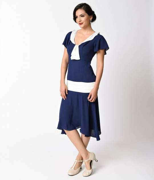 We found a reason to smile in Wilshire, dears! Dreamlike and dainty, The Wilshire is a beautiful 1920s style day dress crafted in an ethereal navy blue woven blend with stunning ivory details. Simplistic short sleeves flutter around the bodice as it makes