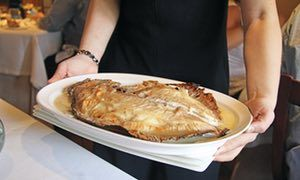 Dish of turbot, on a plate, held at waist level by a waitress at Restaurant Elkano, Getaria, Spain.