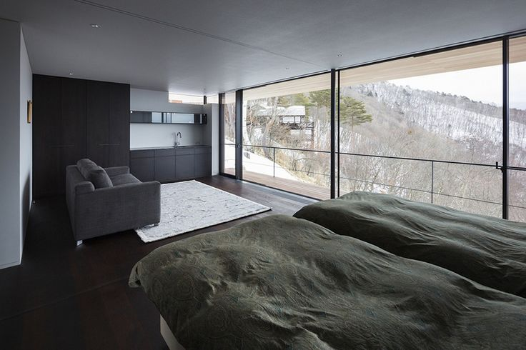 Comfort Twin Beds On Wooden Floor Along With Gray Armchair Towards The Glass Wall With Glass Door To The Balcony Also Black Cabinetry And Sink Minimalist House on the Slope Demonstrates Breathtaking Views Home design
