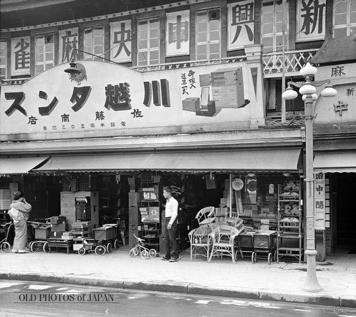 Kyoto, 1934. A furniture store in Kyoto in May 1934. Notice the tricycles and prams. Both are articles that you would not expect at a furniture store. The classical street lamp is a wonderful work of art. Another interesting aspect are the many chairs on display. Western influences have clearly already deeply penetrated the Japanese lifestyle in the early 1930s, only some 80 years after Commodore Perry forced Japan to open up to the world in July, 1853.