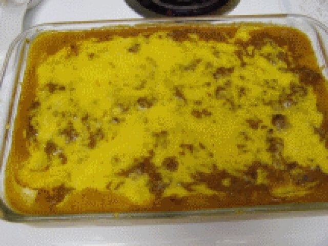 This simple layered enchilada-style casserole is made with ground beef that's simmered in a creamy enchilada sauce and layered with longhorn cheese and corn tortillas. | CDKitchen.com
