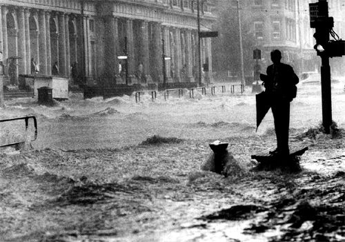 A pedestrian is stranded on a bench as water roars down Elizabeth Street during floods, 1972. Photo: Neville Bowler
